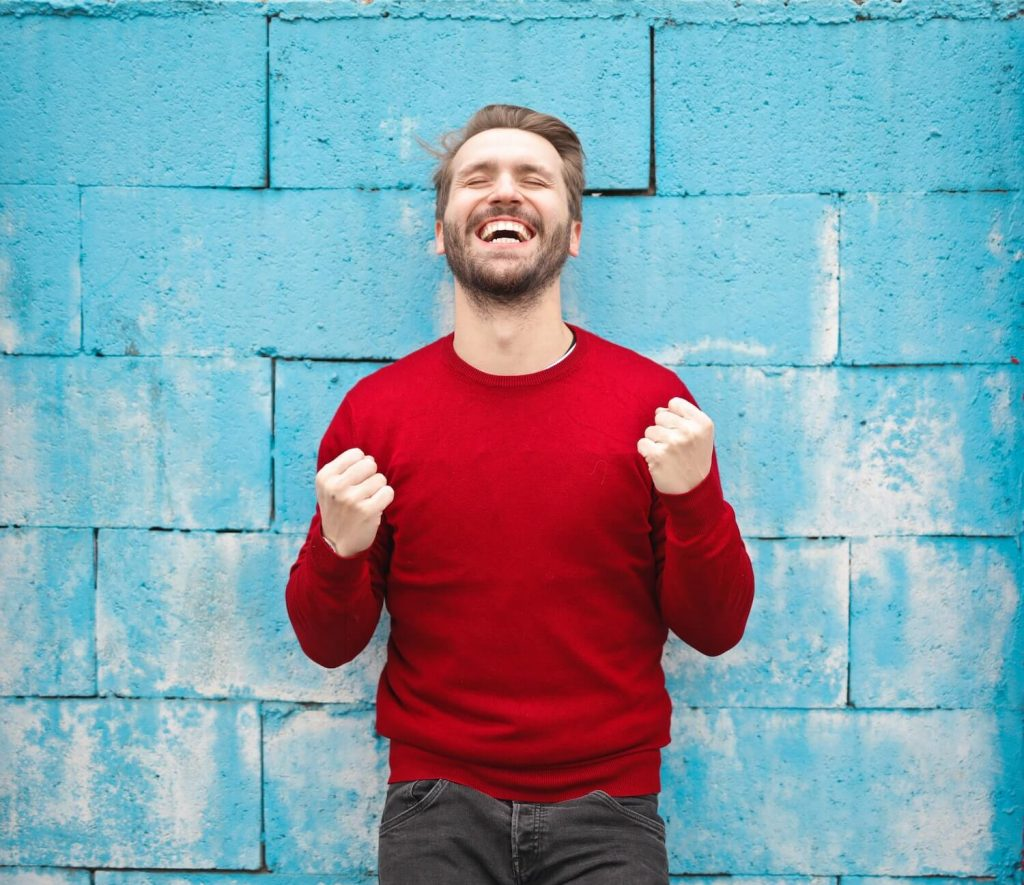 Man in red shirt next to blue wall with excited look on face