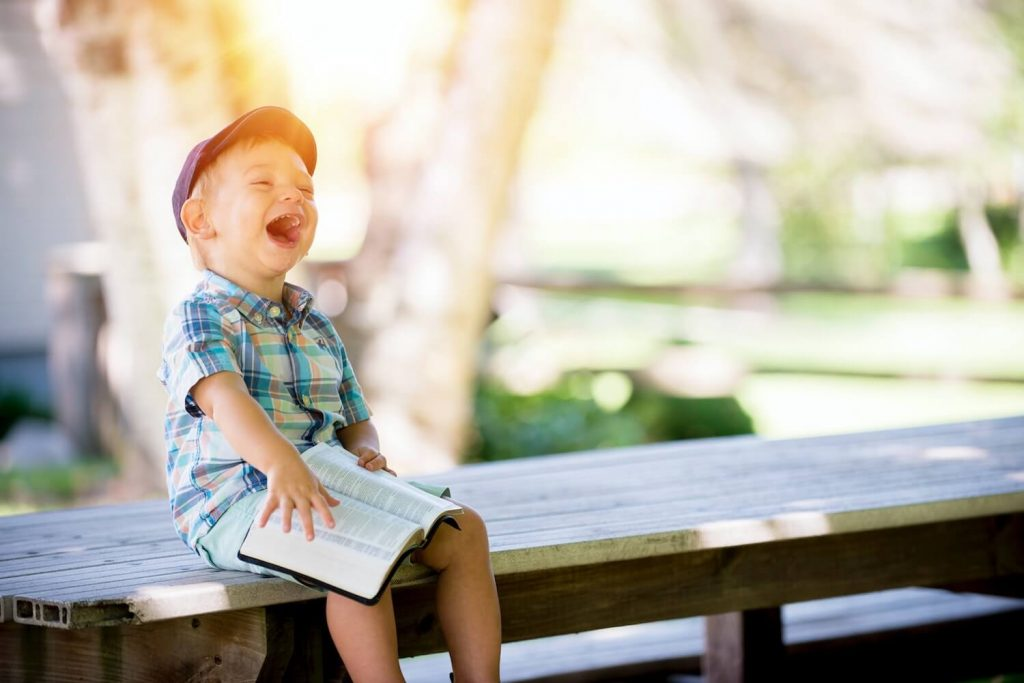 Young boy sitting on bench laughing while reading the Bible