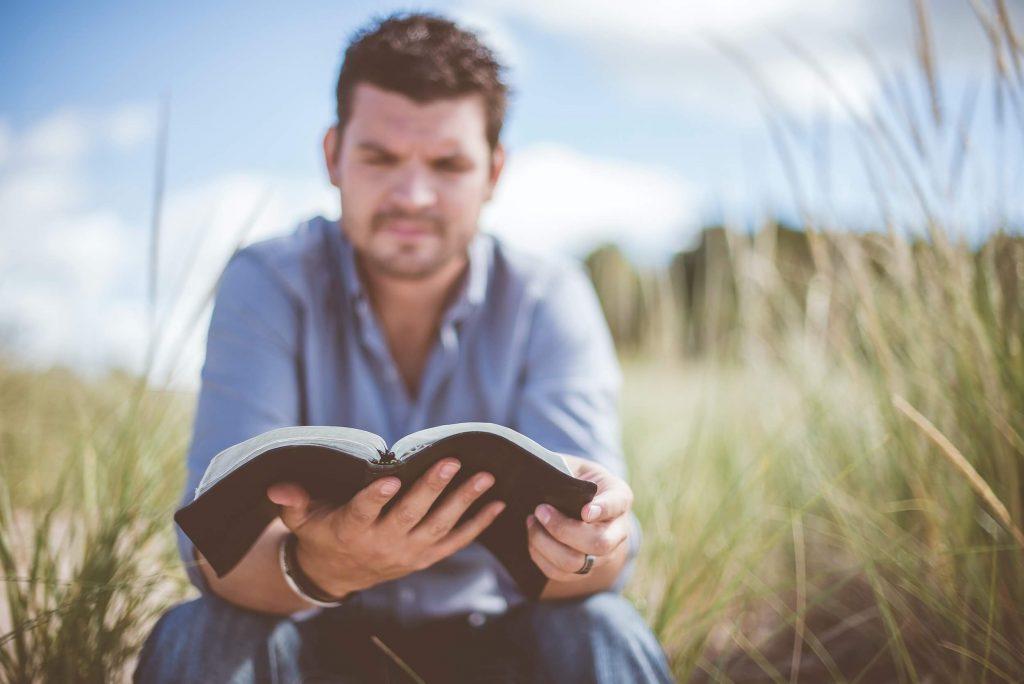 Man sitting in field reading Bible